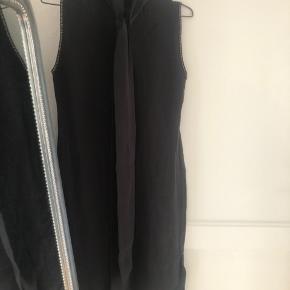 Super fin sort kjole i 100% silke. Fin perlekant langs ærmegab og slidser i begge sider.
