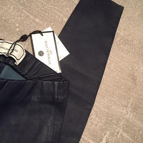 Super bløde skindbukser i stræk-nappa designet til at sidde tæt til kroppen. Den elastiske talje giver ekstra komfort til disse bukser.   Flotteste mørkeblå farve Tætsiddende pasform Elastik i taljen Naturligt stræk 100% lammelæder Skindrens Nypris 5000,-