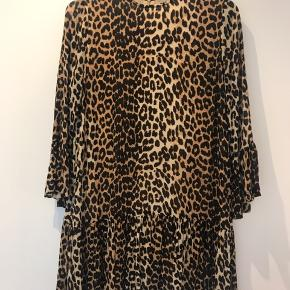 Bliv klar til sommeren med denne leopard kjole fra Ganni! Kjolens snit og facon er et af de populæreste fra Ganni sæson efter sæson. Kjolen har de moderne funnel ærmer og skørt samt det fashionable leopard print. Kjolen lukkes med lynlås bagpå og har stretch i stoffet. Der er er lille ubetydeligt hul i underkjolen (se billede) 100% viscose Normal pasform Maskinvask ved 30 grader