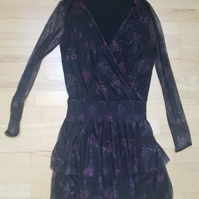Fin let kjole fra Gestuz i sort med lilla blomsterprint. Kjolen har en dyb V-udskæring, smock-detalje ved taljen/hoften, og fint feminint skørt.  Skal i polyester/elastan og for i viskose. Brugt ganske få gange, men uden synlig slitage.