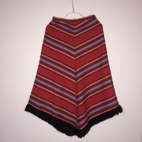 Vintage ulden nederdel med flot vævet mønster og frynser. Måler 67 cm i taljen. God stand!