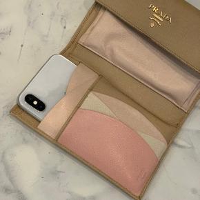 PRADA • CLUTCH/WALLET 1150,-  🔴Nedsat til 1000,-🔴  Et sommer must have! 😍 Mini clutch/pung i beige/sand nuance med klassisk Prada hardware logo på fronten. Kan bruges som almindelig clutch/pung og som den fineste bælte taske! Der kan udover mønter, kort og sedler også findes plads til mobilen. På billedet er der sat en iPhone X i lommen 🙌🏼 Som det fremgår af billederne har den mindre slid.  L 15 cm H 10 cm   Flere billeder i kommentar.   Bælte medfølger ikke.
