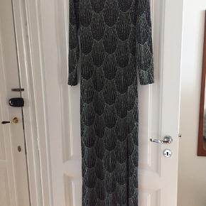 Flot, gulvlang kjole med sølv glimmer i muslinge-mønster. Tætsiddende.  Der er slids i venstre side.  Aldrig brugt.