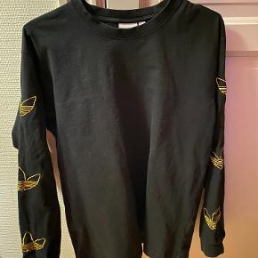 Flot langærmede shirt fra Adidas. Har nogle flotte guld Adidas logoer på ærmerene. Sælger den da jeg ikke passer den mere.