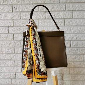 Vintage taske fra 60'erne. Lavet i ægte læder med en flot hang. Har brugs tegn, men fremstår stadig meget flot og velholdt. Tørklædet kan matches til resten af outfitet.  OBS - Tørklædet medfølger ikke!