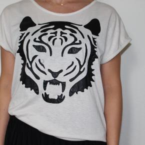 """T-shirt med """"læder"""" tigerhoved sælges. Kan afhentes i Odense C eller sendes via """"køb nu"""". V. køb af flere stk. gives gode rabatter :)"""