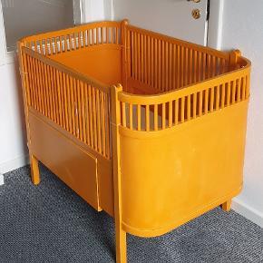 Tremmeseng, Original Junoseng (udtræksseng) - bedre kendt som lille-Per sengen ☺  Farven er den originale gul/orange, som man kunne få sengen i for knapt 60-70 år siden, hvorfor sengen selvfølgelig har brugsmærker og patina.  Derudover fejler den ingenting og er brugt til 1 barn.  Fakta: ▪️Fra dyre og røgfrit hjem.  ▪️Originale tremmer og bund. ▪️Madras til baby medfølger ved køb. ▪️Junior dyne + pude medfølger ved køb.