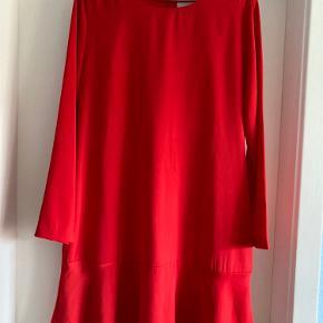 Smuk rød kjole med flæser for neden og lynlås i ryggen. Lækkert, glat stof som falder rigtig flot og sjældent har brug for at blive strøget. Du kan se mere om den her: https://www.jydepotten.dk/vare/26589-karen-by-simonsen-roed-kjole