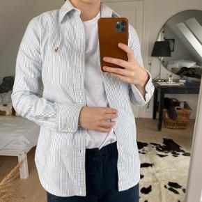 Ralph Lauren skjorte i lyseblå/hvide striber  Str. XS  Modellen er custom fit  Aldrig brugt med prismærke  Sælges da den er for lille til mig