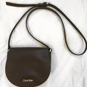 Crossbody fra Calvin Klein. 1 år gammel. Mørk brun med falmet logo og minimum slitage. 800kr fra ny. Original dustbag medfølger.