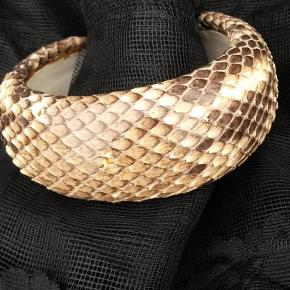 Varetype: Armbånd pytonslange Størrelse: se tekst Farve: slange  To stive armbånd af pytonslange. Begge foret med lyst skind. Det mindste er 6x6 cm og er næsten glat - billed 1 og forside Det største er 6x6,5 cm og med lidt mere tydelige skel - billed Indersiden er ens for begge armbånd.  Prisen er pr. stk.