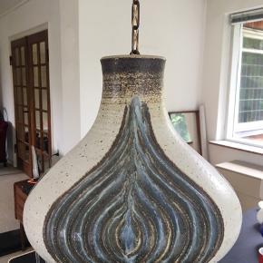 Rigtig fin keramik lampe. Grålig i farven med noget brunt og blåt mønster på siden. Hænger i en kæde. Diameter under lampen 30 cm. Prisen er til forhandling