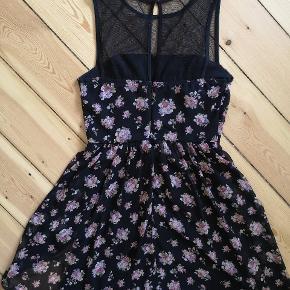 """Sort kjole med blomstermønster og fede detaljer som mesh-stof til overdelen. Kjolens underdel består af to lag: et underskørt (så den ikke er gennemsigtig) og et florlet lag mesh-stof I sort med blomster på. Den sidder flot til foroven og ned til tajlen, hvor skørtet begynder og """"puffer"""" en smule ud af og giver en flot tajle. Skørtet går til lige over knæene.   Den er købt i New York, og er en kjole, jeg altid har fået en del positive kommentarer ✌️  Brugt, men har ingen brugstegn, og sælges, da jeg ikke kan passe den mere."""