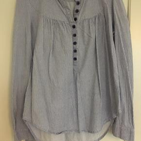 Fin skjorte i feminint snit. Tynder striber og blå knapper. Fejler intet.