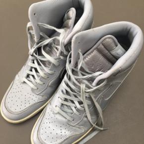 Sølv Nike med kilehæl str 40,5.   Næsten ikke brugt men lidt pletter på snørebånd.   Np 1000,- Mp 300,- pp ved mobilepay