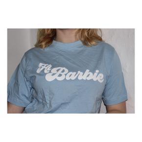 Lyseblå aqua t-shirt med hvid tekst.  Størrelse small.  Aldrig brugt.