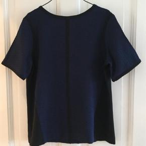 Varetype: Bluse Farve: Navy  Smuk bluse i navy og sort. Blusen har lynlås bagpå.  Aldrig brugt.