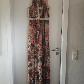 Helt ubrugt, smuk gulvlang kjole. Kjolen er skåret under brystet, hvilket giver den en smukt snit/fald.  Flotte varme farver.  Perfekt som gallakjole, sommerkjole eller til en festlig lejlighed såsom bryllup mm.   Desværre købt for lille 😔 Derfor sælger jeg den.