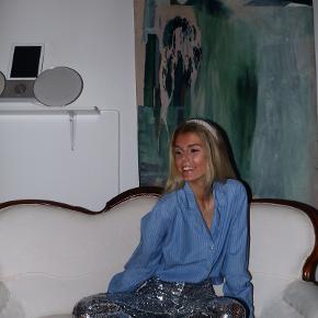 - BENYT 'KØB NU' FUNKTIONEN, VED KØB -  Blå hvidstribet skjorte i pyjamasinspireret look. Skjorten har en V-hals med skjortekrave og gennemgående knappelukning foran. Kan både bruges til afslappet hverdagsbrug eller som nattrøje.   ○ Mærke: Ukendt - intet indvendigt mærke ○ Størrelse: Ukendt - intet indvendigt mærke; ligner dog en str. M (se mål) - Ærmelængde: 64,5 centimeter  - Skulderbredde: 47 centimeter - Brystmål: 54 centimeter - Taljemål: 53 centimeter - Længde:  68 centimeter ○ Fit: Løs ○ Stand: Brugt og vasket et par gange ○ Fejl/Mangler: Ikke umiddelbart ○ Materiale: Ukendt - intet indvendigt mærke; føltes dog som bomuld