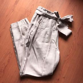 Løse bukser med bindebælte i en støvet rosa lilla farve fra H&M conscious. Lynlås i siden.  Materialet er lyocell, polyester og bomuld. Livvidde = 42 og så x2 når det er hele vejen rundt. Længden er 95cm.   Kommer fra et ikke rygerhjem.  Sender gerne via dao, køber betaler fragt. Forhandler gerne om prisen. 😊