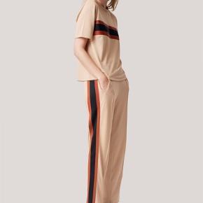 Gannis cool og comfy bukser til det hele. Farven er sandfarvet med røde og blå galoner.  God stand. Fitter godt og er superbehagelige at have på. Nypris 900;