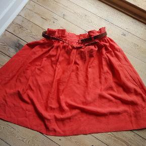 Orange knælang nederdel med brunt bælte.