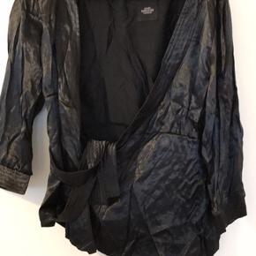 Flot sort binde bluse fra Mads Nørgaard i 63% viscose og 37% polyester, den er ca 50 cm lang