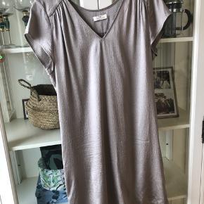 Kjole i silke med let shine. Farven er varm grå