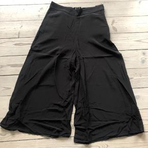 Worn 1 time. 100% viscose. Højtaljede flotte sorte bukser, 3/4 længde. Falder pænt og flatterende. Vie i benene.