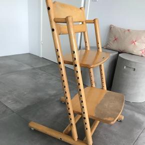 Barnestol af ukendt mærke. Minder om trip trap stolen. Sæde og fodplade kan justeres i højden. Trænger til slibning og lakering.