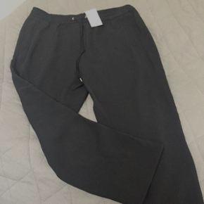 Flotte sorte bukser med elastik talje, fra ikke ryger hjem. Aldrig brugt . Str 42..  ny pris 249kr. Fra HogM.