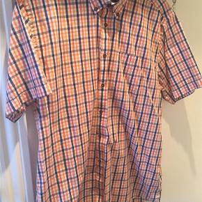 Varetype: Skjorte Farve: Ternet orange og blå Oprindelig købspris: 399 kr.  Denne skjorte er som ny. Vasket 2 gange. Kortærmet og med lille lomme. Hvid bund og med tern i 2 forskellige orange farver og en meget mørk blå. Rigtig flot til jeans. Sælges da vi ska ha ryddet op i skabet.