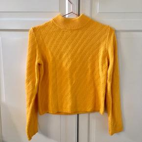 Gul sweater fra Selected Femme. Den er lavet af 60 % bomuld og 40 % akryl.