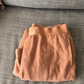 Calvin Klein hyggebukser i farven pudder rosa/peach. Normal i str. Kun brugt et par gange. Mega behagelige hyggebukser, og sælges fordi de er lidt for store.