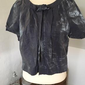 Fin lille jakke, farven er mørk blå-grå Lukkes med en trykknap øverst 89 % linen og 11 % Polyamid