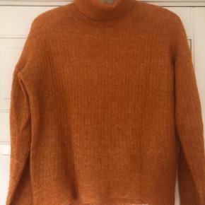 Lækker sweater med rullekrave. I flot orange farve lidt meleret. Detalje at sweateren er 6 cm kortere foran.  Brystvidde 104 cm, længde midt bag 59 cm, længde midt for fra halsudskæringen 50 cm