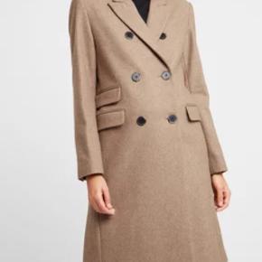 Smuk og klassisk camel / beige farvet dobbeltradet frakke str 40.  Perfekt overgangsfrakke med smuk pasform. Brugt max 5 gange!   Materiale: 60% uld, 35% polyester, 5% øvrige fibre For: 100% polyester