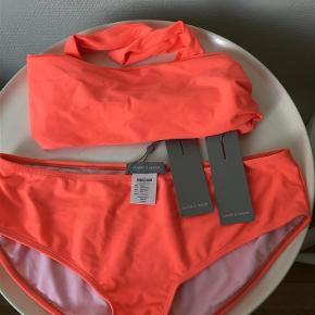 Skarp stærk Koral / Orange farvet bikini fra Samsøe i str. S.  Stor i str., så har sat den til S/M i str. Feltvælger. Passes af 36-38. Aldrig brugt og stadig med mærker/tags. Modellen hedder Bahia. Toppen er bandeau model, som skal bindes og totallængde er ca 125 cm. Trussen måler ca 22 cm i længden. Oprindelig detail pris ca 600, men jeg har købt den som prøve til 300,-  Bikini Farve: Koral Oprindelig købspris: 600 kr.