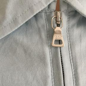 Flot Prada polo i lyseblå med fede detaljer- sender gerne flere billeder. Kan både bruges af mænd og kvinder. -tjek min profil ud-