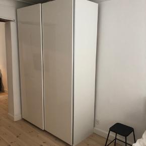 IKEA pax skab med skydelåger i hvid højglans. Indrettet med hylde, bøjlestang, skuffe og vaskekurv i den ene side og hylde, bøjlestang, 3 skuffer og skoskuffe i den anden.   Mål: b 150 x d 66 x h 236 cm  Nypris omkring 6000  Kun 6 måneder gammelt og fejler intet.   Kan afhentes og skal selv skilles ad på Østerbro