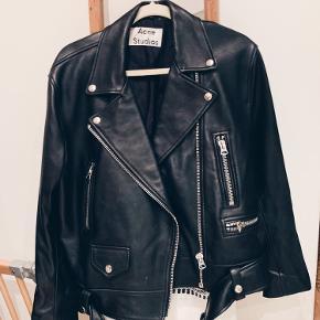 Acne Studios 'klassiske bikerjakke er en tidløs investering, der passer til alt fra kjoler til T-shirts. Lavet i smidigt sort læder.    -Størrelse 38  -Sort læder  -Asymmetrisk lynlås foran  - 100% læder (lam)  for: 52% viskose, 48% bomuld  Nypris: 10.000,-  Sælger: 6.500,-