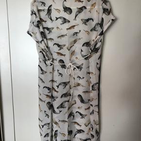 str 36, men rummelig i størrelse. Passes også en str M Sød sjov silke kjole med fiskemotiver Der er bindebånd som kan bindes foran eller på ryggen Længde : 91 cm Brystmål : 50x2 cm Bytter ikke