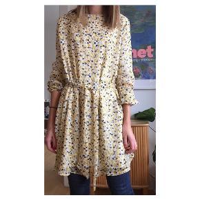 Fin gul blomstret kjole Med bindebånd bagpå Elastik i ærmerne så den kan sættes som man ønsker Jeg har den på på billederne og er xs.