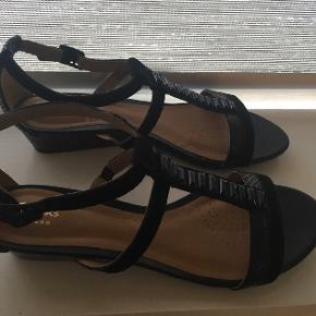 """#30dayssellout Smukke, sorte """"Playful fox"""" sandaler fra Clarks i str 40 - flot ruskind/læder design og med kilehæl på ca 3,5 cm. Rigtig lækre og klassisk design, kun prøvet på få gange indenfor, derfor er standen sat som """"aldrig brugt"""" da der intet slid/brugsspor er og de som sagt aldrig har været rigtig brugt. Den originale æske følger også med og som man kan se på billedet er selve """"sko holderne"""" også med i æsken og har været på sandalerne det meste af tiden da de jo som sagt aldrig har været i brug.  Jeg købte dem for ca. 900 kr.   Hvis de skal sendes, betaler køber fragten.  Mvh Betina Thy"""