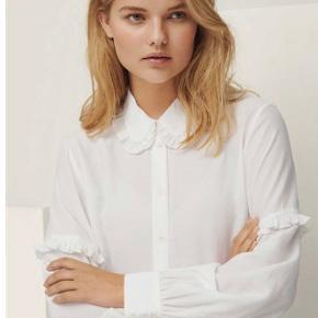 Moss Copenhagen Frances Melody Shirt med fine flæser i kraven og på ærmerne. Lækker kvalitet, som er meget blød at have på. Udsolgt over alt.