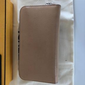 Rummelig pung fra Fendi i nude lakeret læder. Orange indeni. Små tegn på slid men inden ridser.  Nypris: 3500,-