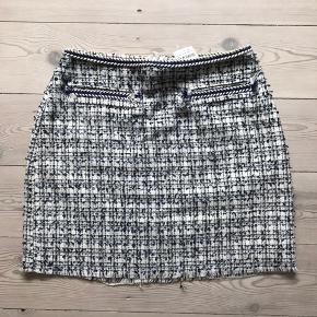Super fin Bouclé mini nederdel med hvid, blå og sort farvesammensætning. Stadig med prismærke, købspris 249kr.