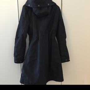 G Star raw mørke blå vinter jakke/ frakke med stor hætte som kan knappes mindre.Jakken har bindebånd i taljen . Str medium. Lidt slid anes ved syning i ærme. Farven som er blevet til utydelig lys streg i syning. Den hedder small men svare til m