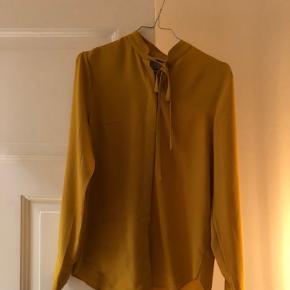 Skjorte/bluse fra H&M med bindebånd ved halsen. Blusen er aldrig brugt.