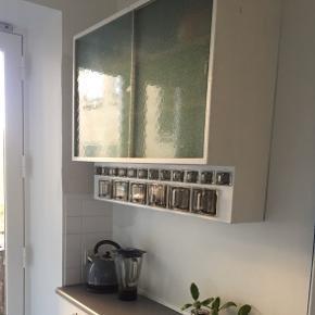Smukt, vintage/retro hængeskab til køkkenet med glas glidelåger og glasskuffer i to lag og to størrelser. Har lidt slitage, men står smukt, klar til brug. Tre af de små og en af de store glasskuffer har mistet et hjørne, men de øvrige er i sjældent god stand. Lidt slibning og en ny gang maling, vil få det til at stå knivskarpt igen. Indvendigt er lavet flere ophængshuller da væggene i de lejligheder jeg har haft det hængende har været udfordrende ;-)  Har hængt hos min morfar og mormor, dernæst i mit barndomshjem og har fulgt mig de sidste 15 år. Nu er det tid til at det skifter ejer, og kan få masser af gode år i er nyt hjem :-)   Højde 82,5 cm Længde 106 cm Dybde (ved låger) 31 cm Dybde (ved skuffer) 18 cm